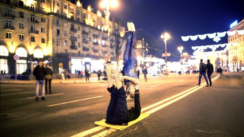 男性和女性做的acro瑜伽在街道上在市中心,极端爱好,体育 库存照片