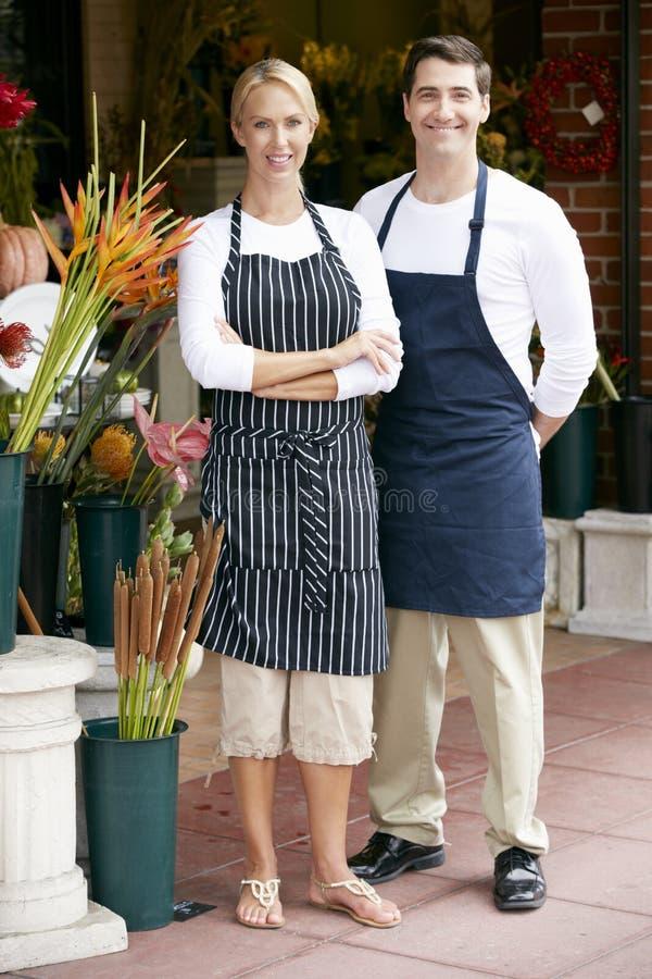 男性和女性卖花人外部商店画象  免版税库存图片