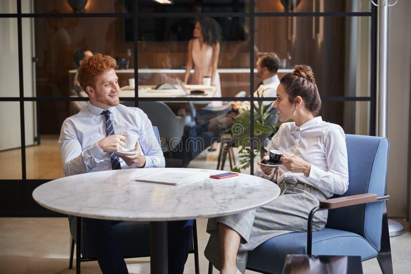 男性和女性同事谈话在咖啡在办公室咖啡馆 库存图片