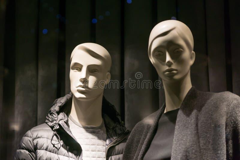 男性和女性时装模特在穿黑暗的衣裳的商店窗口里 r 免版税库存照片