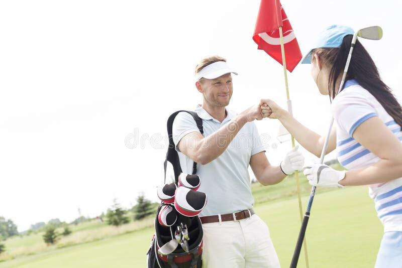 男性和女性朋友给高五在高尔夫球场 免版税库存图片