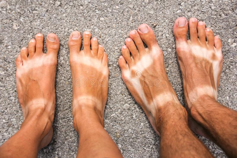 男性和女性被晒黑的脚 库存照片