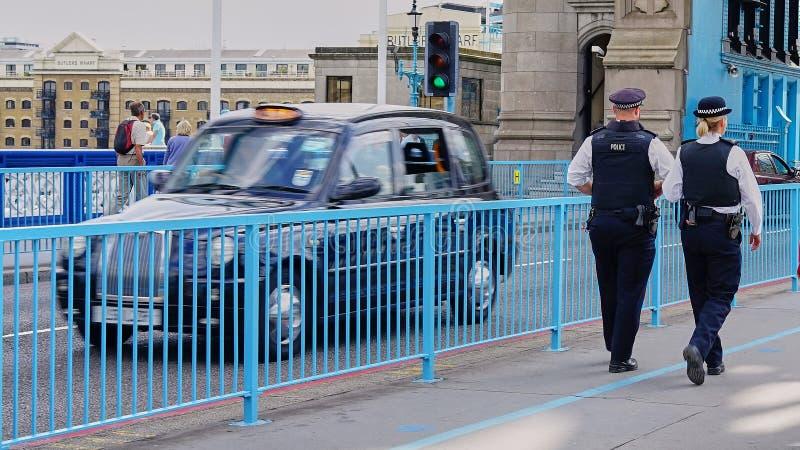 男性和女性警察巡逻伦敦塔桥 免版税库存照片