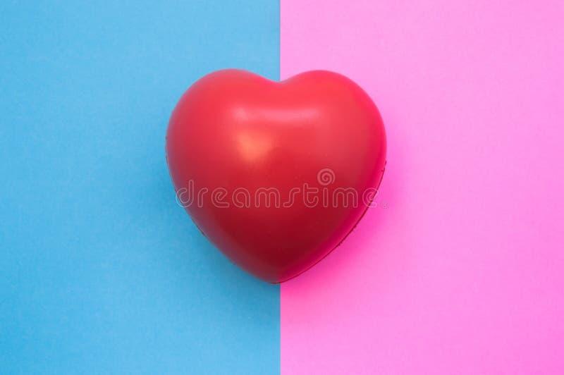 男性和女性重点 心脏在象征男人和妇女的两种颜色在桃红色的背景中说谎-蓝色和 医疗特点,单 免版税库存图片