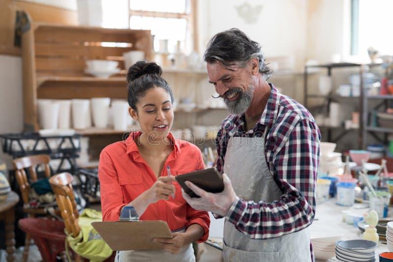 男性和女性陶瓷工谈论在平板电脑 库存照片