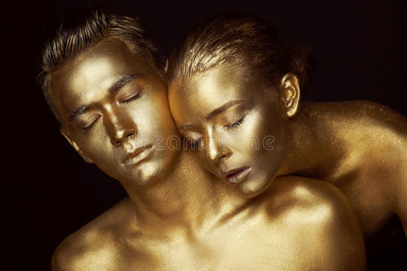 男性和女性面孔 妇女` s头在一个人的肩膀说谎 在金油漆绘的所有, a的感觉 免版税库存照片