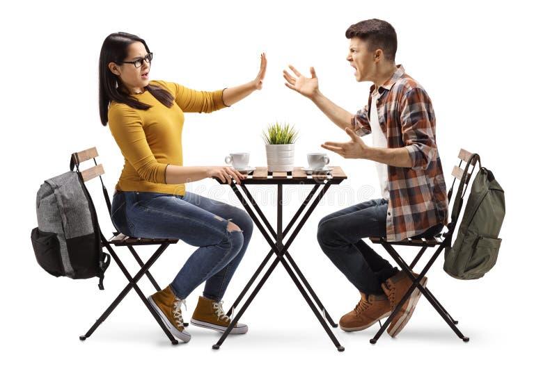 男性和女生争论在咖啡馆 免版税图库摄影