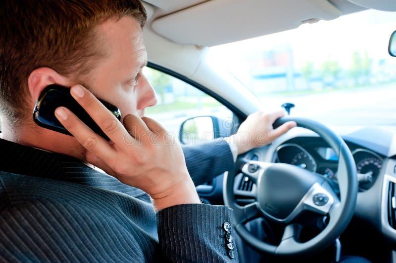 男性商人谈话在手机,当驾驶时 库存图片