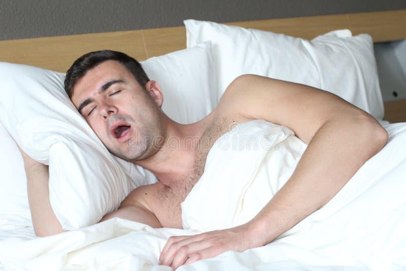 男性在与睡眠停吸混乱的床上 免版税库存图片