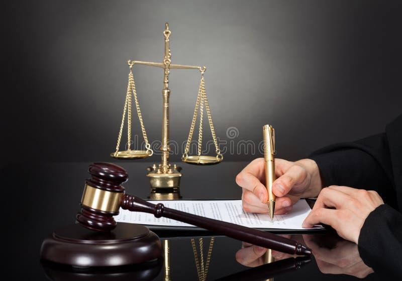 男性在书桌的法官签署的文件 库存图片