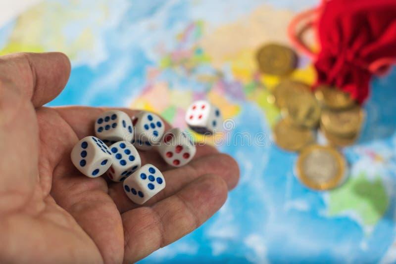 男性在桌上的手投掷的模子与世界地图和金钱 世界的归属的概念 世界秩序 免版税库存照片