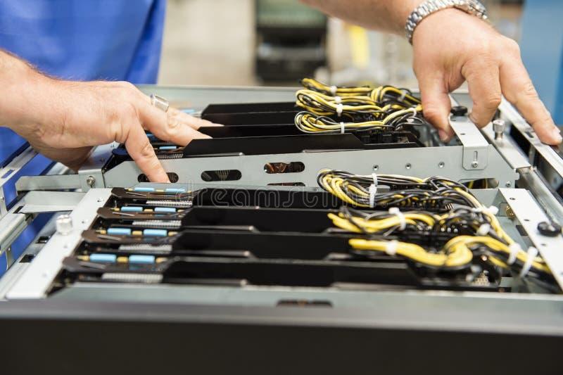 男性在电子工业的技术员审查的计算机卡片槽的播种的图象 免版税图库摄影