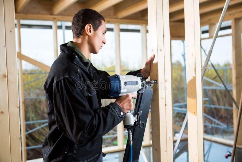 男性在站点的木匠钻木头侧视图  库存照片
