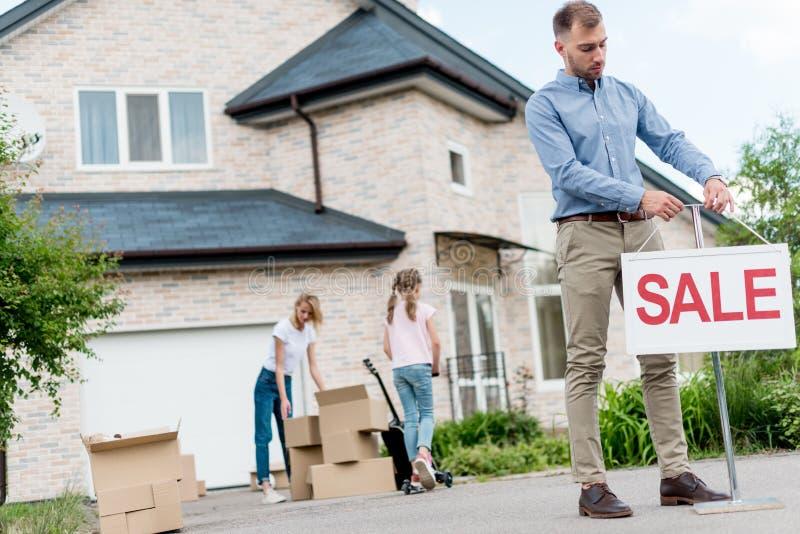 男性在调迁的人前面的地产商垂悬的销售标志 库存图片