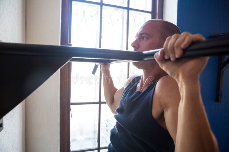 男性在酒吧的运动员实践的引体向上由窗口 免版税图库摄影