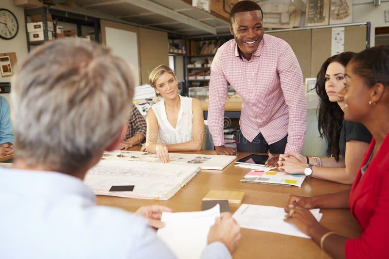 男性坐在表上的建筑师上司主导的会议  免版税库存照片