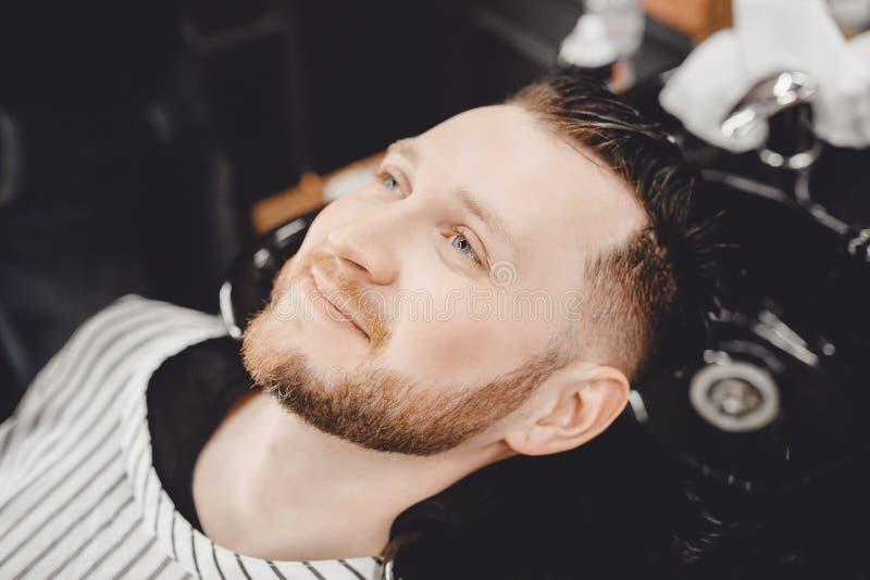 男性客户洗涤他的头发理发店和微笑,时髦称呼 免版税库存照片