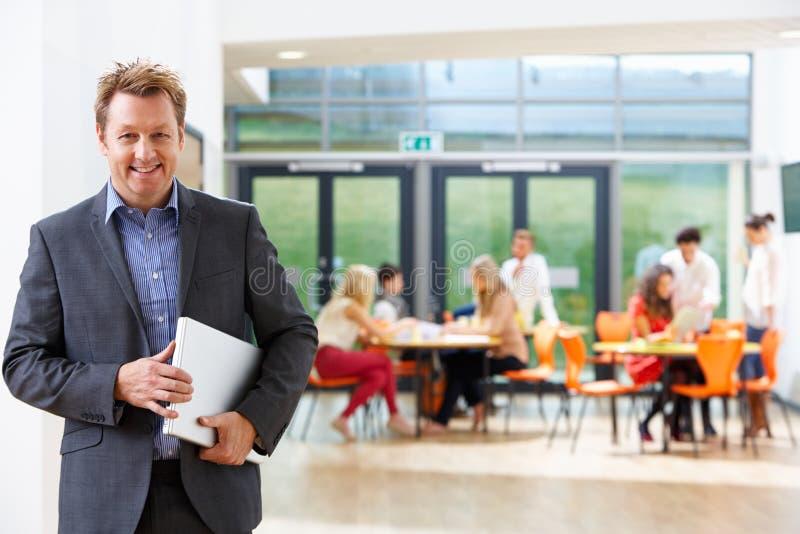 男性家庭教师在有膝上型计算机的教室 库存图片