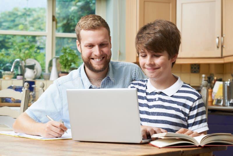 男性家庭有研究的家庭教师帮助的男孩 免版税库存照片
