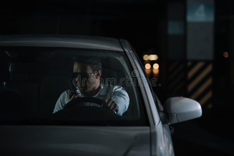 男性密探正面图做监视和使用有声电影walkie的太阳镜的 库存照片