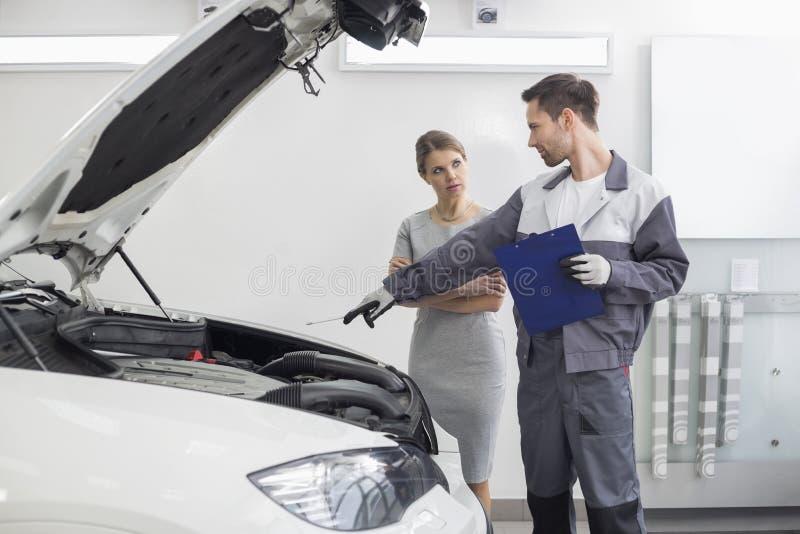 年轻男性对女性顾客的安装工解释的发动机汽车维修车间的 免版税库存照片