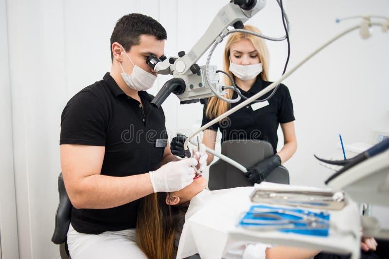 男性对待耐心牙的牙医和女性助理与牙齿工具-显微镜、镜子和钻子 免版税库存照片