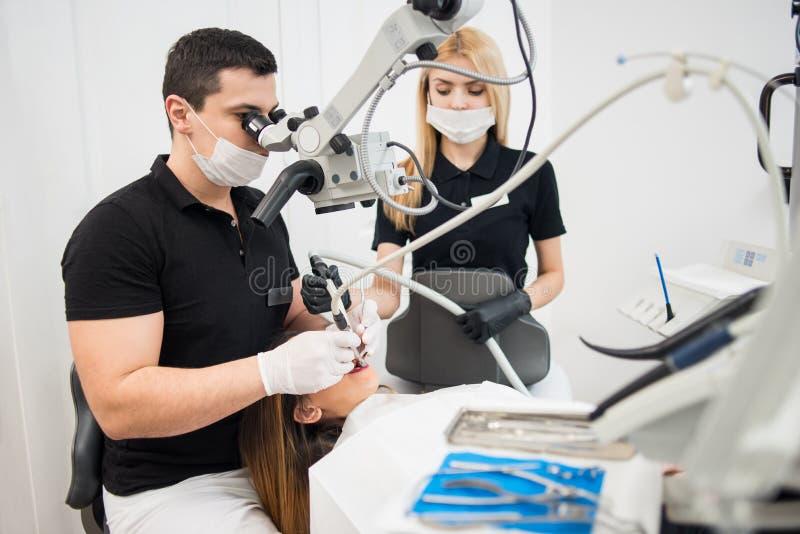 男性对待耐心牙的牙医和女性助理与牙齿工具-显微镜、镜子和钻子 库存图片