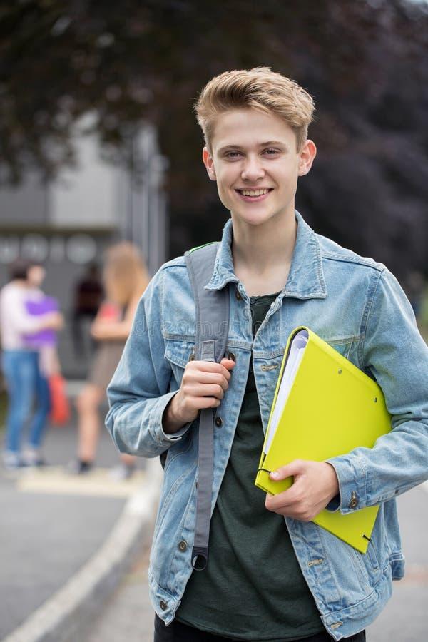 男性少年学生画象在教学楼之外的 免版税图库摄影