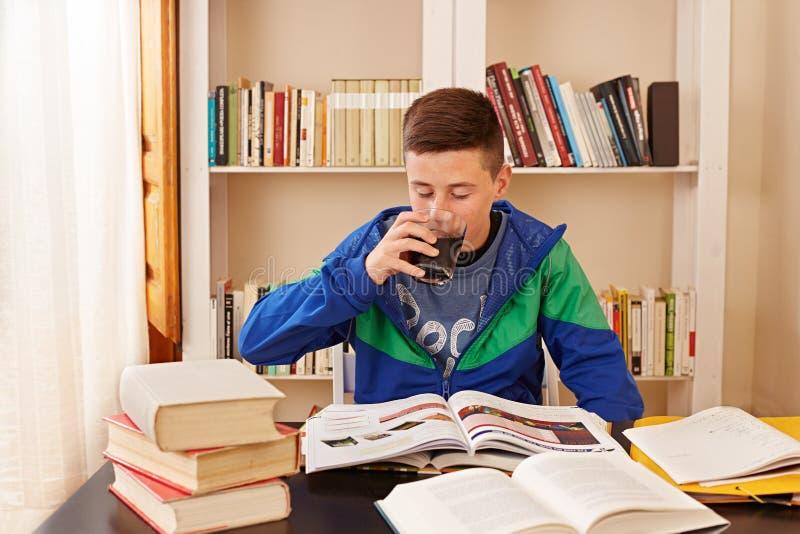 男性少年饮用的焦炭,当学习时 免版税库存图片