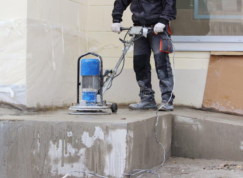 男性工作者与金刚石磨床一起使用,擦亮在办公楼前面的门廊 水泥地板和co 免版税库存照片