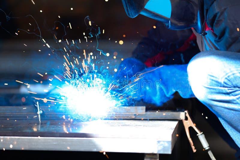 男性工作者佩带的建筑手套和面具焊接metall建筑,蓝色焊弧 免版税图库摄影