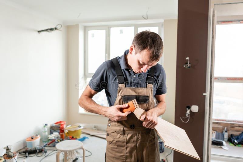 男性工作者削减有沙纸的层压制品的委员会 安装新的木层压制品的地板 修理的概念在房子里 库存图片