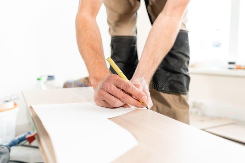 男性工作者应用标号于切开的委员会用electrofret看见了 安装新的木层压制品的地板 免版税库存照片