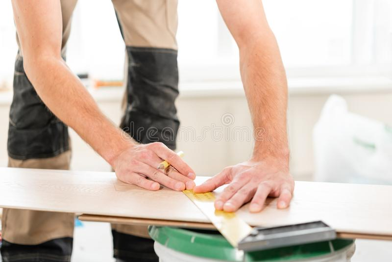 男性工作者应用标号于切开的委员会用electrofret看见了 安装新的木层压制品的地板 库存图片