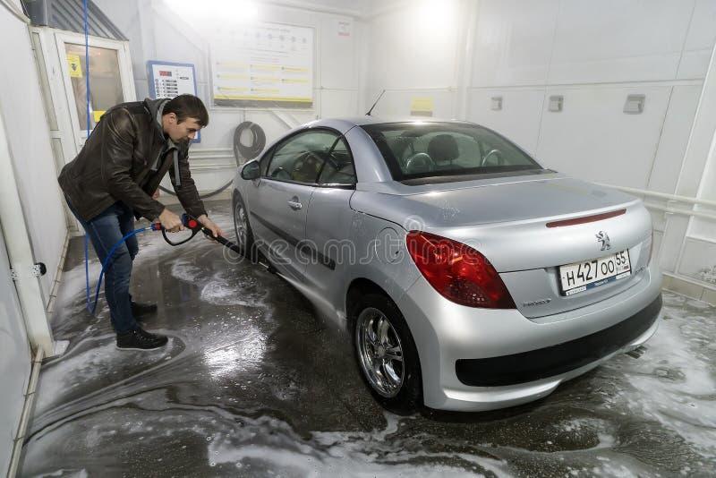 男性工作者洗涤有高压洗衣机的汽车 库存图片