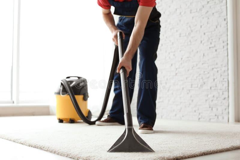 男性工作者清洁地毯以真空 免版税库存照片