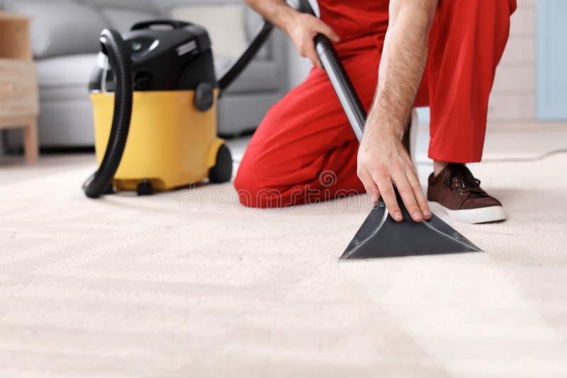 男性工作者清洁地毯以真空 图库摄影
