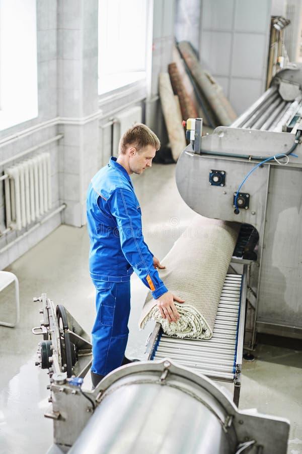 男性工作者清洁从一台自动洗衣机得到地毯并且运载它在干衣机 免版税库存图片