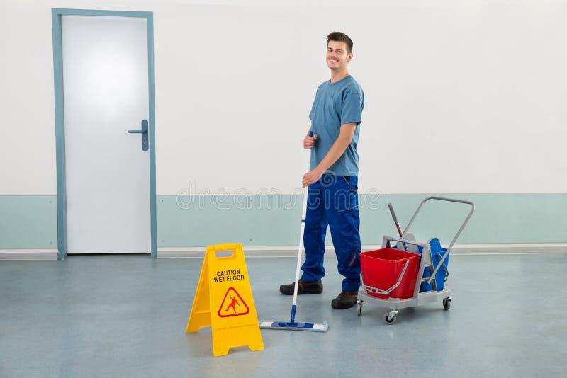 男性工作者用擦地板的清洁设备 免版税库存图片