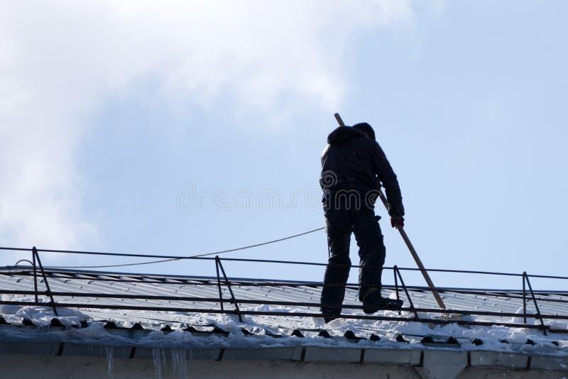 男性工作者队从雪清洗大厦屋顶与在巩固佛经传送带的铁锹  免版税图库摄影