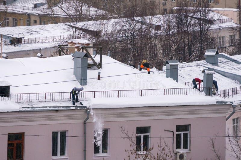 男性工作者队从雪清洗大厦屋顶与在巩固佛经传送带的铁锹  库存图片