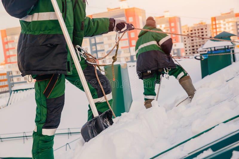 男性工作者队从雪清洗大厦屋顶与铁锹 库存照片