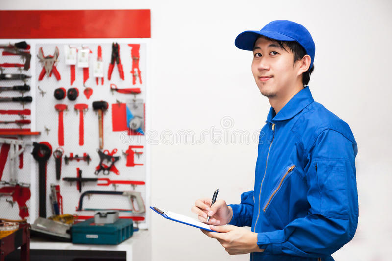年轻男性工程师在技工的工作用工具加工贮藏室 免版税库存图片