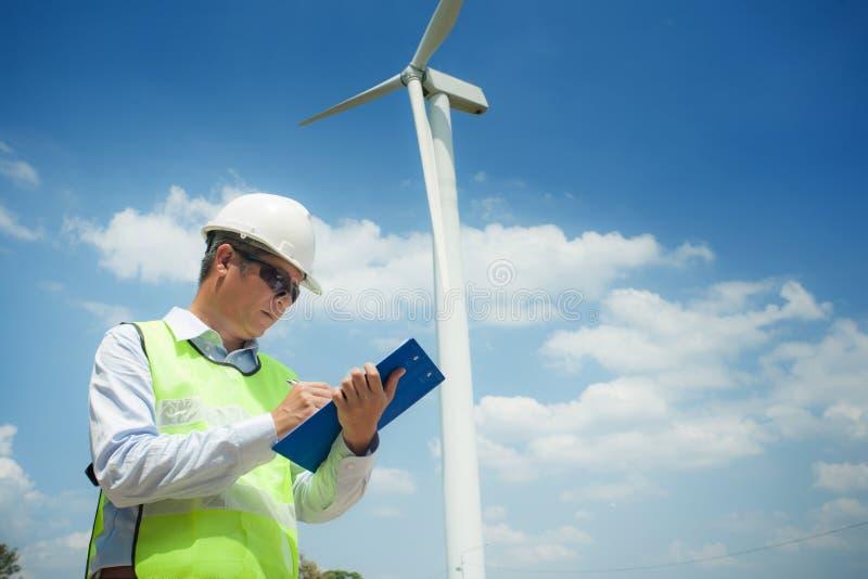 男性工程师或tecnician在工作风轮发电机驻地,风力概念 免版税库存照片