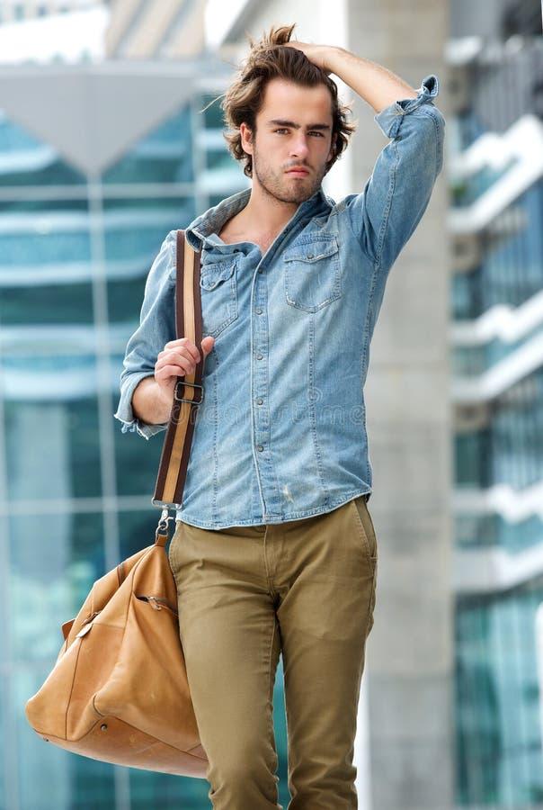 男性式样摆在与旅行袋子户外 库存照片