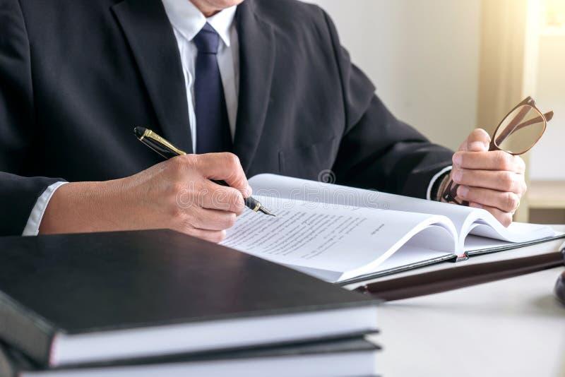 男性律师或法官与法律书籍一起使用,惊堂木,报告c 免版税库存照片