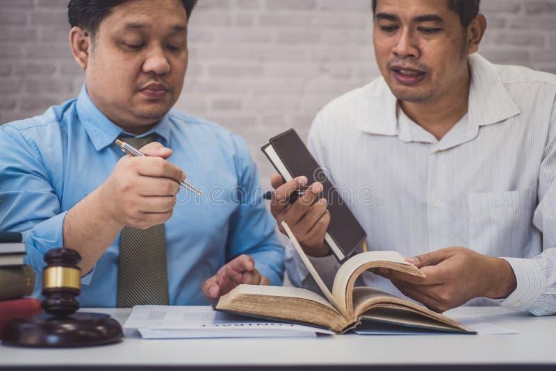 男性律师教新的律师和谈论与合同纸和木惊堂木在桌上在法庭 正义和法律, 免版税库存照片
