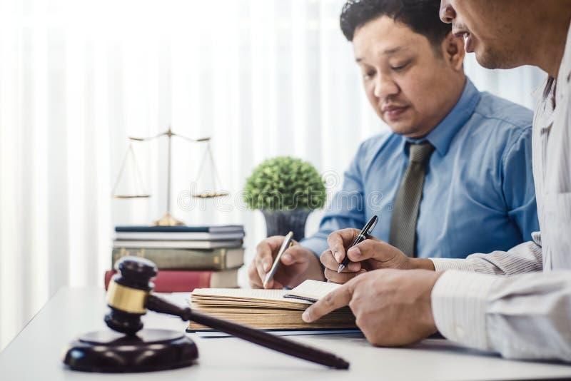 男性律师教新的律师和谈论与合同纸和木惊堂木在桌上在法庭 正义和法律, 免版税库存图片