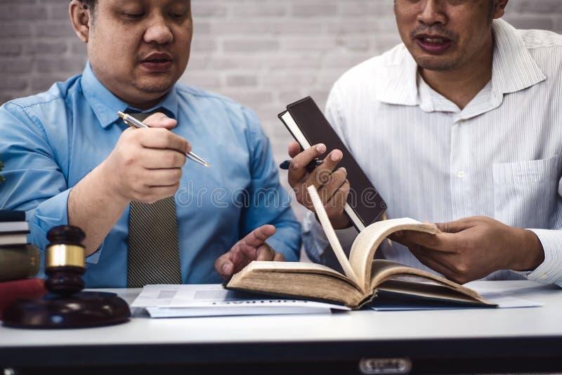 男性律师教新的律师和谈论与合同纸和木惊堂木在桌上在法庭 正义和法律, 图库摄影