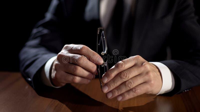 男性律师递拿着镜片,与被指责的人的私人会谈 免版税图库摄影